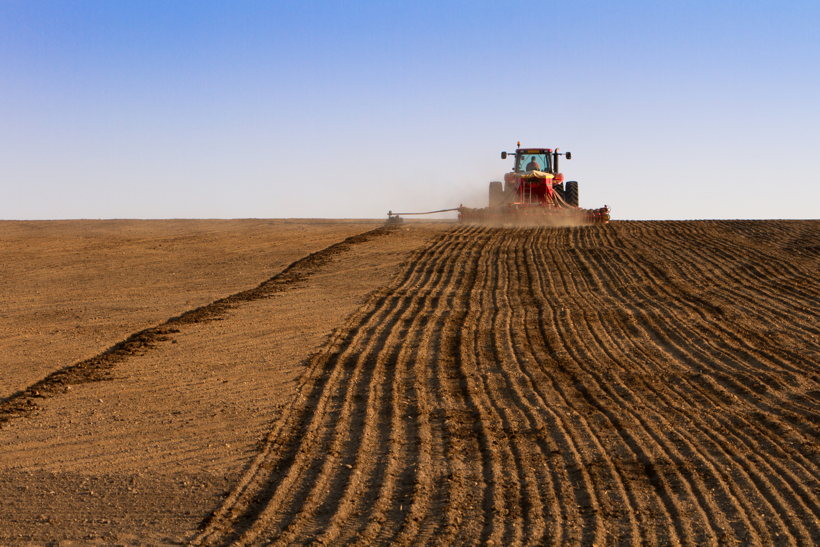 Dirt field with a tractor plowing it